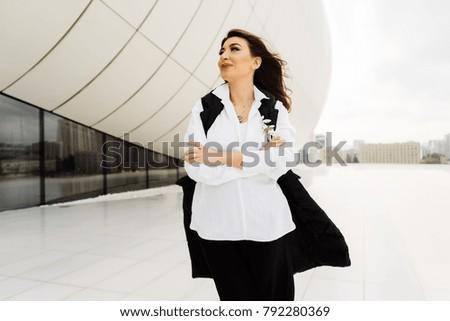 attractive beautiful girl in a black suit walks around the city of Baku