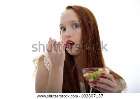 Attractive beautiful long haired woman eating edible fruits in a glass cup and holding a spoon