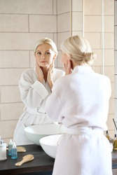 Attractive beautiful mid age adult 50 years old blonde woman standing in bathroom of SPA hotel touching face, looking at reflection in mirror doing daily morning beauty routine. Skin care concept.