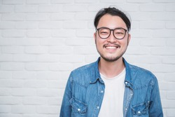 Attractive beautiful positive asian man - close up portrait asian nerdy man. Handsome nerd Japanese guy wearing glasses with big smile isolated on white background.