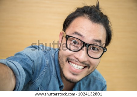 Attractive beautiful smiling positive nerd man selfie with his smartphone. Close up portrait asian beard hairy nerdy man with crossed arms isolated on white background.