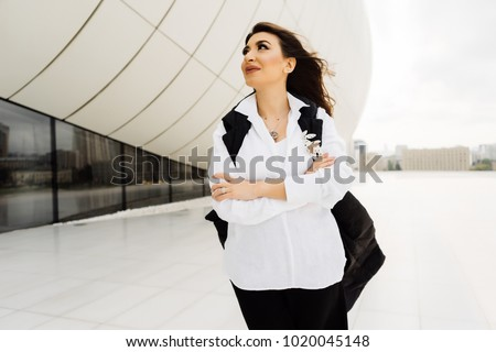 attractive beautiful woman in a white shirt walking around the city of Baku