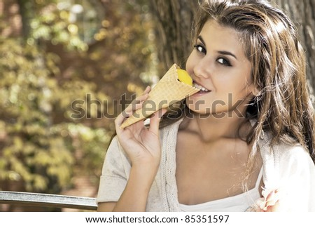 attractive beautiful young brunette woman eating ice cream