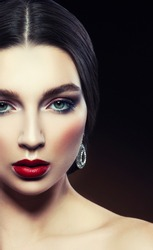 Attractive beauty girl portrait with jewelry and make-up over dark background