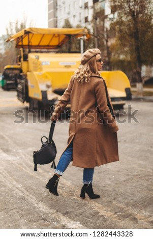 Attractive beauty woman walking near big yellow truck. Full height photo of fashionable female wearing casual outfit and backpack. Street style. Girl wears beige coat, beret, blue jeans and black boot #1282443328