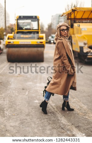 Attractive beauty woman walking near big yellow truck. Full height photo of fashionable female wearing casual outfit and backpack. Street style. Girl wears beige coat, beret, blue jeans and black boot #1282443331