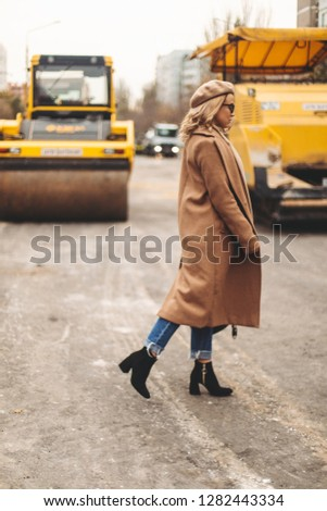 Attractive beauty woman walking near big yellow truck. Full height photo of fashionable female wearing casual outfit and backpack. Street style. Girl wears beige coat, beret, blue jeans and black boot #1282443334