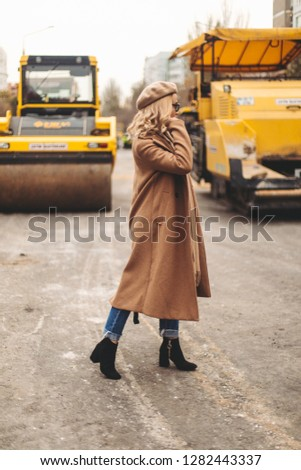 Attractive beauty woman walking near big yellow truck. Full height photo of fashionable female wearing casual outfit and backpack. Street style. Girl wears beige coat, beret, blue jeans and black boot #1282443337