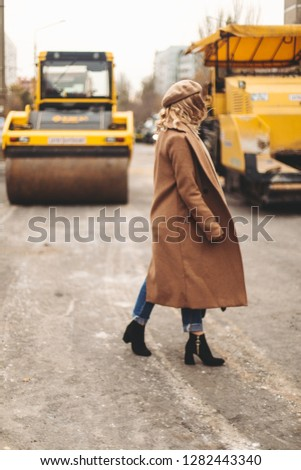 Attractive beauty woman walking near big yellow truck. Full height photo of fashionable female wearing casual outfit and backpack. Street style. Girl wears beige coat, beret, blue jeans and black boot #1282443340