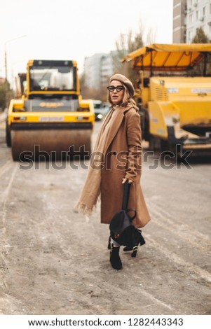 Attractive beauty woman walking near big yellow truck. Full height photo of fashionable female wearing casual outfit and backpack. Street style. Girl wears beige coat, beret, blue jeans and black boot #1282443343
