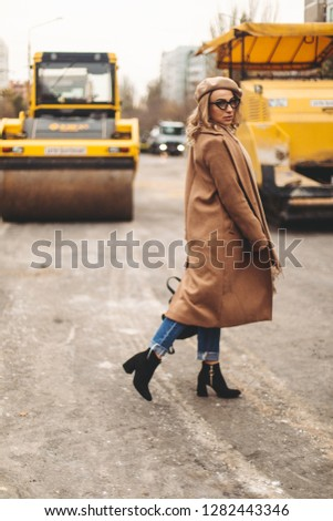 Attractive beauty woman walking near big yellow truck. Full height photo of fashionable female wearing casual outfit and backpack. Street style. Girl wears beige coat, beret, blue jeans and black boot #1282443346