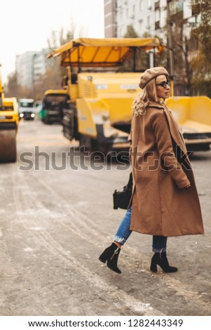 Attractive beauty woman walking near big yellow truck. Full height photo of fashionable female wearing casual outfit and backpack. Street style. Girl wears beige coat, beret, blue jeans and black boot #1282443349