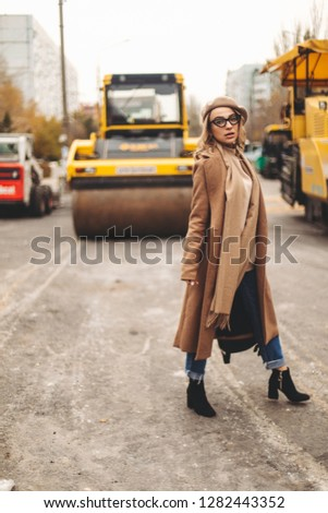 Attractive beauty woman walking near big yellow truck. Full height photo of fashionable female wearing casual outfit and backpack. Street style. Girl wears beige coat, beret, blue jeans and black boot #1282443352