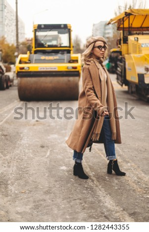 Attractive beauty woman walking near big yellow truck. Full height photo of fashionable female wearing casual outfit and backpack. Street style. Girl wears beige coat, beret, blue jeans and black boot #1282443355