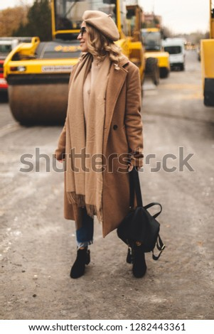 Attractive beauty woman walking near big yellow truck. Full height photo of fashionable female wearing casual outfit and backpack. Street style. Girl wears beige coat, beret, blue jeans and black boot #1282443361
