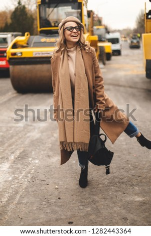 Attractive beauty woman walking near big yellow truck. Full height photo of fashionable female wearing casual outfit and backpack. Street style. Girl wears beige coat, beret, blue jeans and black boot #1282443364
