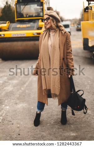 Attractive beauty woman walking near big yellow truck. Full height photo of fashionable female wearing casual outfit and backpack. Street style. Girl wears beige coat, beret, blue jeans and black boot #1282443367