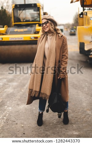Attractive beauty woman walking near big yellow truck. Full height photo of fashionable female wearing casual outfit and backpack. Street style. Girl wears beige coat, beret, blue jeans and black boot #1282443370