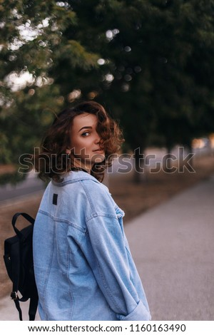 Attractive beauty woman walking on the street while wearing blue jeans. photo from back and girl is turn around.