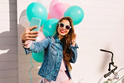 Attractive birthday girl smiles shyly while making a selfie at the holiday party. Charming young brunette woman in sunglasses taking photo of herself with colorful balloons next to white bicycle
