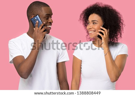 Attractive black couple in white t-shirts holding gadgets talking on mobile phones, looking at each other smiling, isolate on pink blank, communication connection, dating flirting, modern tech concept