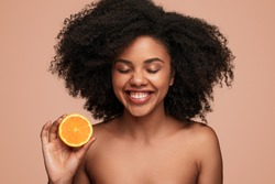 Attractive black female with clean skin laughing with closed eyes and showing half of fresh orange while advertising benefits of vitamin C, in skincare industry against brown background