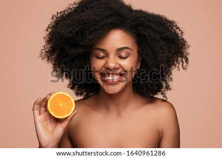 Attractive black female with clean skin laughing with closed eyes and showing half of fresh orange while advertising benefits of vitamin C, in skincare industry against brown background Zdjęcia stock ©