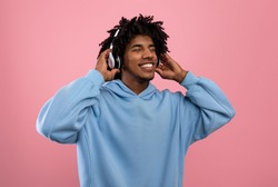 Attractive black teen guy in casual wear listening to music in headphones, closing eyes and relaxing on pink studio background. African American adolescent enjoying favorite melodies