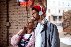 Attractive black woman and her dark skinned stylish friend who listens music with headphones, walk together in street, looks at something with thoughtful expression. People and lifestyle concept.