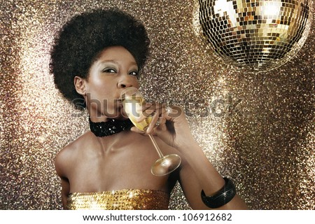 Attractive black woman drinking champagne in a nightclub and drinking champagne next to a disco ball.