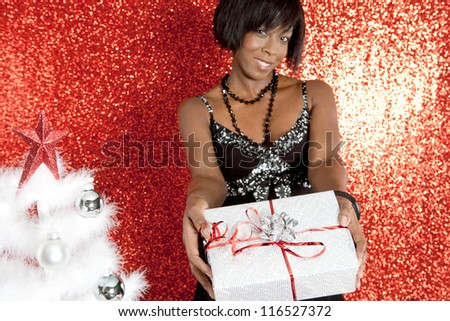Attractive black woman holding a gift box while smiling against a red glitter background at a Christmas party.