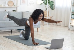 Attractive black woman making morning exercise at home, looking at laptop screen