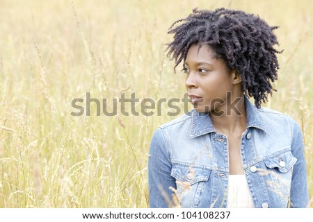 Attractive black woman standing in a long grass field.