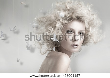 Attractive blond beauty with origami in the background