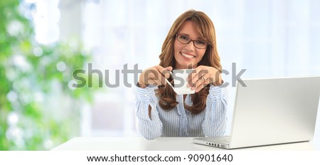 Attractive blond business woman working on her laptop and drinking coffee in her office (blue background)