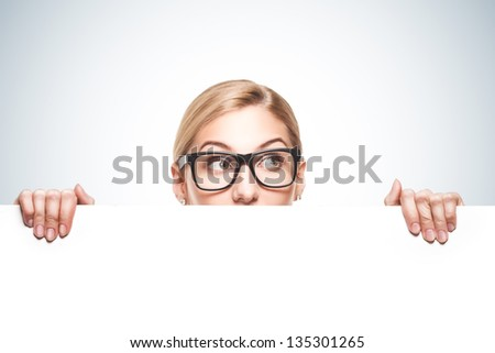 Attractive blond businesswoman looking over top of white sign with copy space isolated on blue background