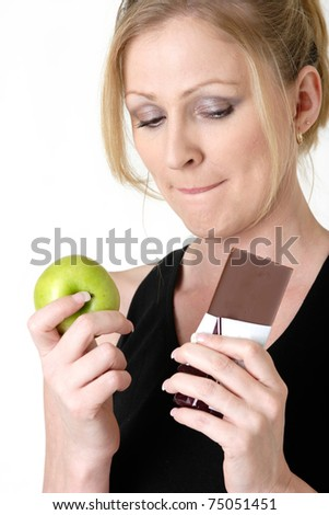 Attractive blond caucasian woman holding an apple and chocolate bar trying to decide which one to eat while biting on her lip