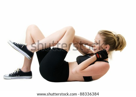 Attractive blond caucasian woman laying on floor wearing workout attire doing stomach crunches or sit ups over white