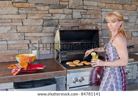 Attractive blond Caucasian woman using a gas barbeque grill in an outdoor kitchen