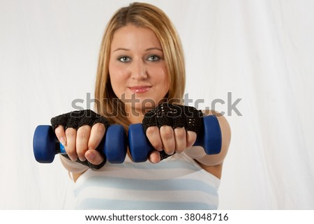 Attractive blond caucasian woman wearing workout attire with hands forward holding two three pound blue weights focus on hands