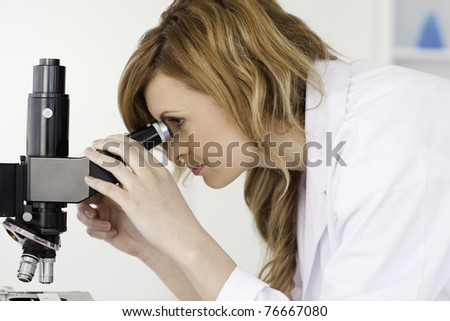 Attractive blond-haired scientist looking through a microscope in a lab