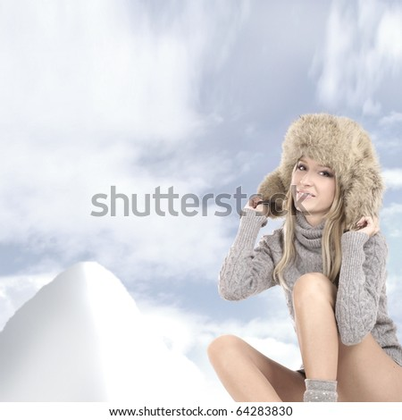 Attractive blond in a winter dress over winter background