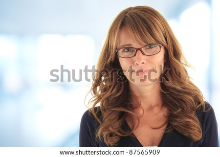 Attractive blond mature business woman in her office with copy space (blue, de-focused background)
