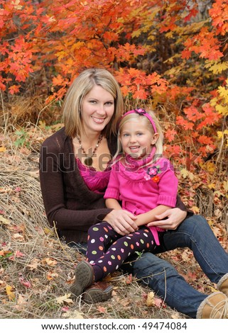 attractive blond mother holding daughter outdoor in fall
