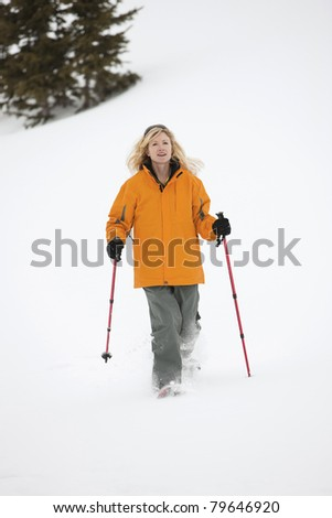Attractive blond  with ski poles snowshoeing.
