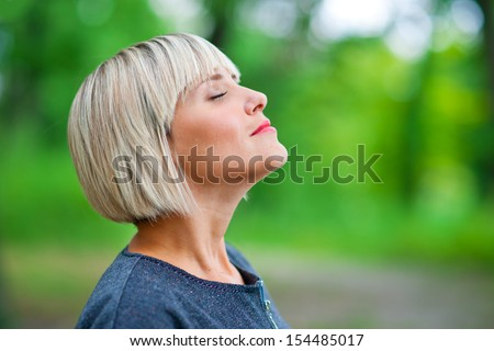 attractive blond woman breathing and relaxing in nature