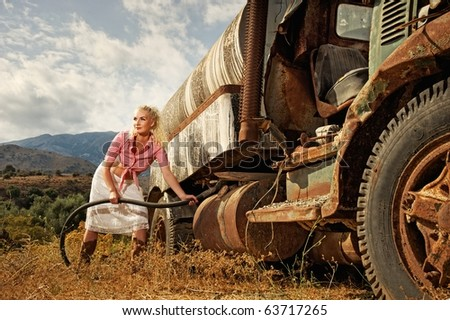 Attractive blond woman filling gas tank of an the old truck - stock photo