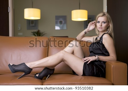 attractive blond woman in black dress sitting on the couch