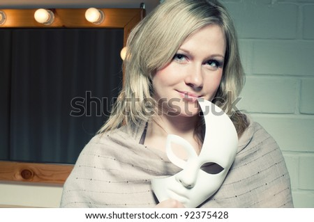 Attractive blond woman with a face mask smiling and looking at camera