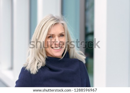Attractive blond woman with a warm happy smile dressed in a warm winter overcoat standing outdoors smiling at the camera